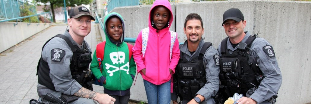 three tactical officers posing with children