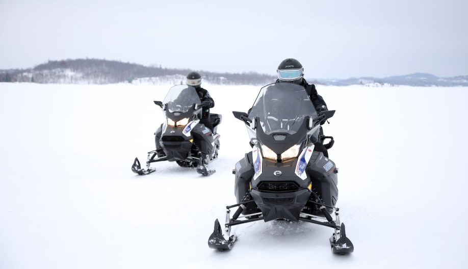 two police officer snowmobiles parked on ice
