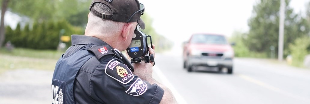 Police officer pointing speedometer at oncoming truck