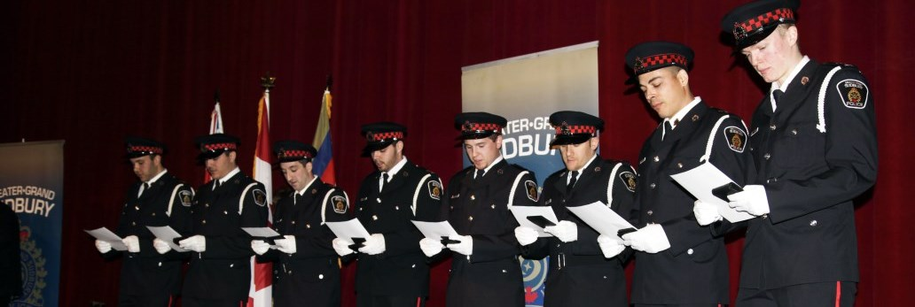 several Auxiliary officers standing in line reading a document