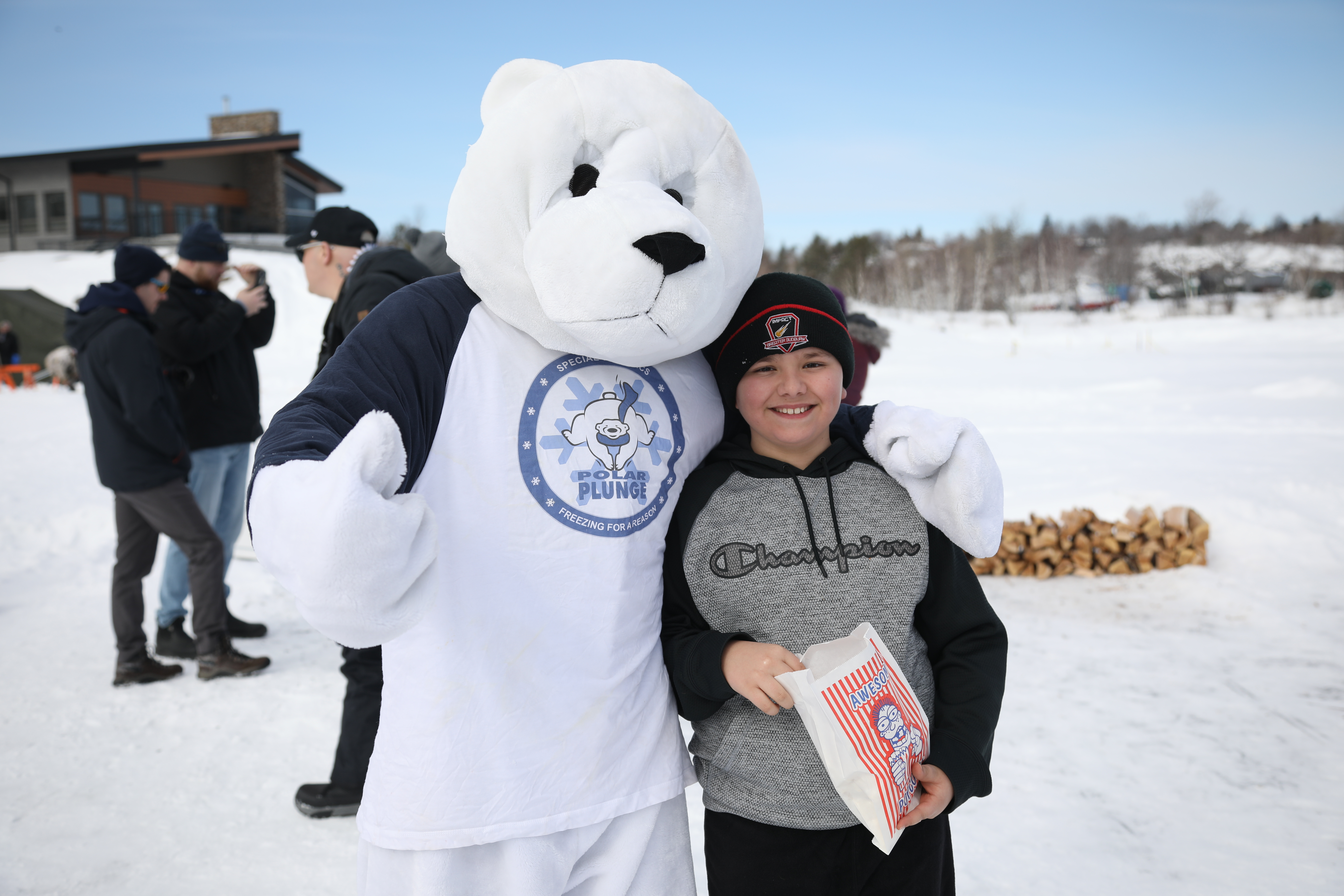 Plungee the Polar Bear mascot standing beside child