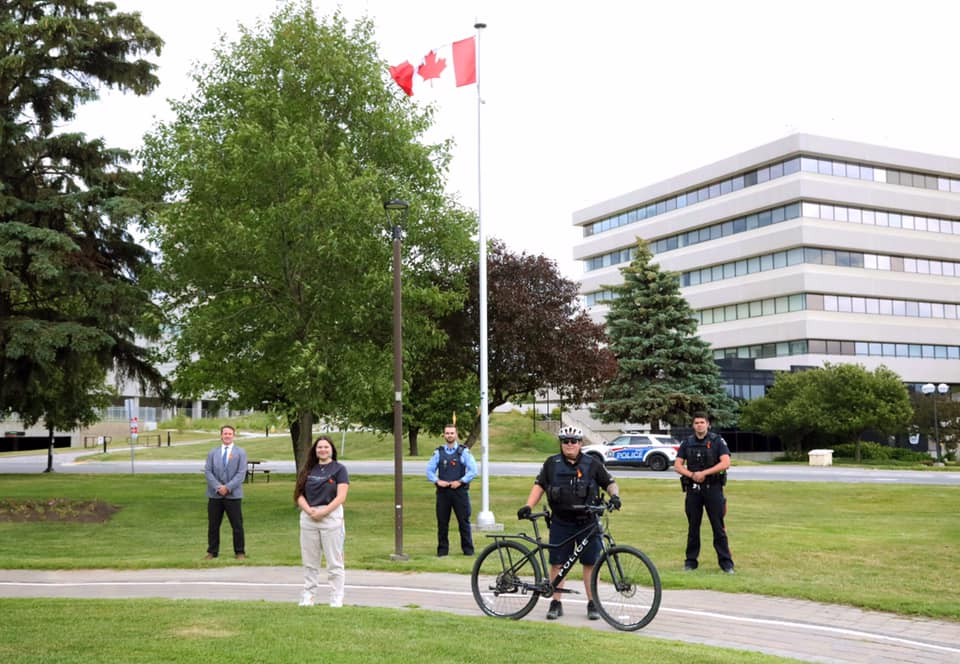 people wearing orange ribbons standing in front of Canadian flag
