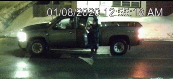 Grey or Silver pick up truck with woman in black jacket standing outside passenger door
