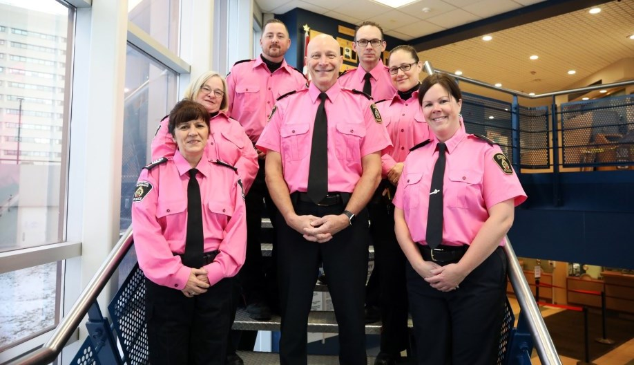 Group of officers in pink shirts standing on staircase